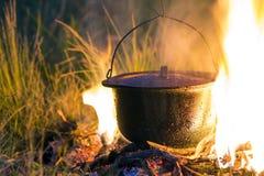 Artículos de cocina que acampa - pote en el fuego en un sitio para acampar al aire libre Imagenes de archivo