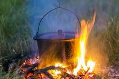 Artículos de cocina que acampa - pote en el fuego en un sitio para acampar al aire libre Imagen de archivo