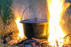 Artículos de cocina que acampa - pote en el fuego en un sitio para acampar al aire libre Foto de archivo