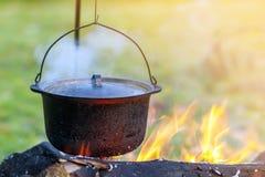 Artículos de cocina que acampa - pote en el fuego en un sitio para acampar al aire libre Fotografía de archivo libre de regalías