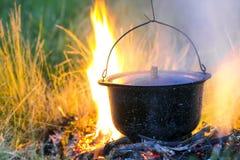 Artículos de cocina que acampa - pote en el fuego en un sitio para acampar al aire libre Fotos de archivo libres de regalías