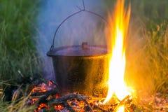 Artículos de cocina que acampa - pote en el fuego en un sitio para acampar al aire libre Imagen de archivo libre de regalías