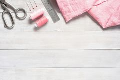 Artículos de costura y tela de lino rosada en la tabla fotografía de archivo