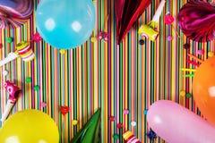 artículos de la fiesta de cumpleaños en fondo rayado con el espacio de la copia Imagen de archivo