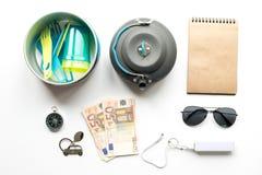 Artículos de la forma de vida del viajero en la opinión superior del fondo blanco de la tabla Foto de archivo libre de regalías