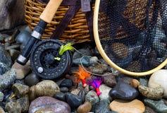 Artículos de la pesca en piedras mojadas del río Fotografía de archivo libre de regalías