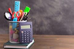Artículos de los efectos de escritorio con la calculadora en el lado izquierdo en la tabla de madera Imágenes de archivo libres de regalías