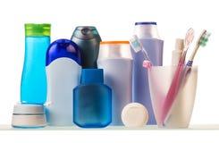 Artículos de tocador, vidrio con los cepillos de dientes y crema dental aislada en el fondo blanco imagen de archivo