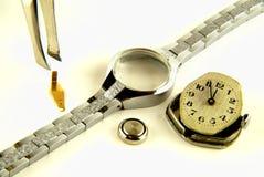 Artículos de un reloj en el fondo blanco imagen de archivo