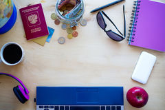 Artículos del viaje, cuaderno, café, PC, globo, manzana, dinero en woode Imagen de archivo libre de regalías