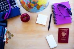 Artículos del viaje, pasaporte, pluma, PC, globo, manzana, dinero en b de madera Fotos de archivo libres de regalías