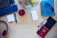 Artículos del viaje, pasaporte, pluma, PC, globo, manzana, dinero en b de madera Foto de archivo