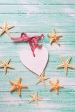 Artículos marinos (estrellas de mar) y corazón decorativo en la turquesa wo imagen de archivo