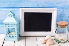 Artículos marinos, vela en linterna decorativa y blackboar vacío Foto de archivo