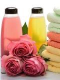 Artículos multicolores para los baños, saunas, balneario: el champú, toallas, florece rosas en un fondo blanco Fotografía de archivo