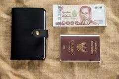 Artículos que viajan: Pasaporte de Tailandia, cartera y dinero tailandés Fotos de archivo libres de regalías
