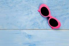 Artículos rosados esenciales del viaje de las gafas de sol de la visión superior en b de madera azul Imagen de archivo libre de regalías