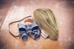 Artículos WWII: George Ribbon, casquillo del forraje, prismáticos Fotografía de archivo