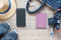 Artículos y accesorios del viaje con el dispositivo móvil en la madera Imagenes de archivo