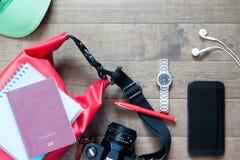 Artículos y accesorios del viaje con el dispositivo móvil en la madera Imágenes de archivo libres de regalías