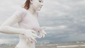 Artístico coberto na menina branca da pintura na costa de mar move-se lentamente video estoque