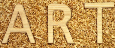 Art. The word ART in the background of sawdust Stock Image