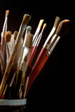 Art. Brushes well used in a Jar on black Royalty Free Stock Photo