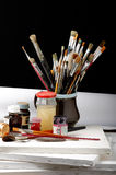Art. Brushes well used in a Jar on black Stock Images