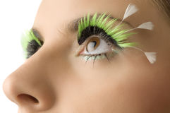 Art and artificial. Close up on the eyes of a young woman with artificial green eyelashes stock photo