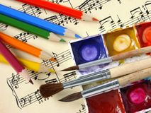 Art background. Color pencils and paints with brushes on the musical notes background Stock Photo