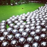 Art balls silver in green pond. Artistically floating spheres royalty free stock photo