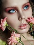 Art beauty girl face closeup with rose in hands on black background. Cosmetics and makeup, body and face skin care, contrast make. Up, big beautiful eyes women stock photos