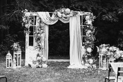 Art black and white photography. Black and white art photography monochrome, beautiful wedding ceremony outdoors. Wedding arch made of cloth and white flowers Royalty Free Stock Photography