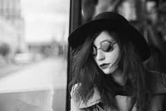 Art black and white photography. Unusual appearance. Woman with curly hair in a blue coat and black round glasses riding on the bus. Black and white art Royalty Free Stock Photo