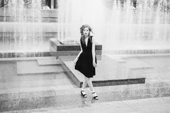 Art black and white photography. Unusual appearance. Woman with long curly hair in a black dress on a background of the fountain. Black and white art monochrome Stock Photos