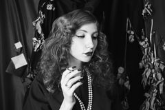 Art black and white photography. Unusual appearance. A woman with long hair in fitting dress with a cigarette in her mouth. Black and white art monochrome Stock Photo
