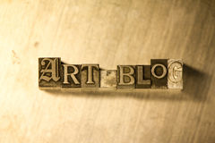 Art blog - Metal letterpress lettering sign. Lead metal 'Art blog' typography text on wooden background Royalty Free Stock Images