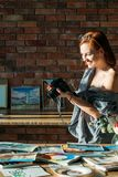 Art blog studio workspace woman painter photo. Art blog. Studio workspace. Smiling woman painter taking photos of watercolor artworks. Copy space on brick wall royalty free stock images