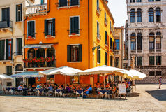 Art blu cafe. VENICE, ITALY - JULY 7, 2007: Tourists rest and eat in Art blu cafe. The Art Blue Café rises in the center of Venice in Campo Santo Stefano just stock image