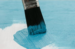 Art brush cover the wood with a thick layer of bright blue paint Stock Images