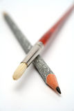 The art brush is crossed with a celebratory brilliant pencil Royalty Free Stock Photo