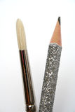 Art brush near to a celebratory brilliant pencil for plotting. 2 Royalty Free Stock Photography