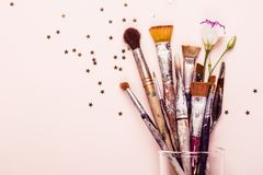 Art Brush Set and scattering of gold stars on pale pink background.  stock photography