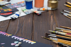 Art brushes and oil paints and sketches are laid out on a dark wooden surface Stock Photos