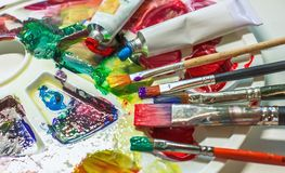 Art brushes and paints for painting on the used palette with paints close-up. royalty free stock photo
