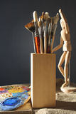Art brushes in a wooden glass. With a palette and model on a dark background Royalty Free Stock Photography