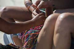 Art on a Caribbean Beach-Embroidery. Seller`s hands on a nice Mexican beach.Embroidery Stock Image