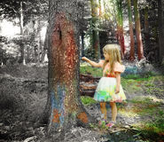 Art Child Painting Black and White Forest. A little girl is painting trees with colors in a black and white forest for an creativity or imagination concept about royalty free stock images
