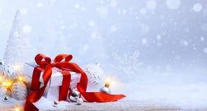 Art Christmas balls and gift box on snow Stock Photo