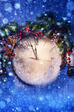 Art Christmas Eve and New Years at midnight. New Years clock and fir branches covered with snow royalty free stock photo